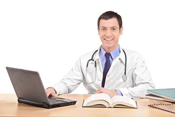 Doctor sitting at a desk and working on laptop