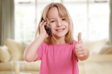 hübsches kleines Mädchen mit Handy und Daumen hoch