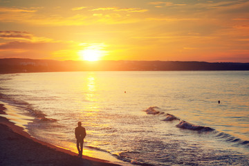 Man walking alone on the beach at sunset. Calm sea