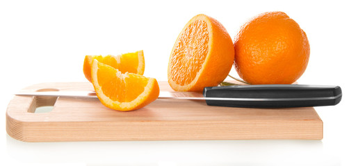 Orange sliced with knife on cutting board