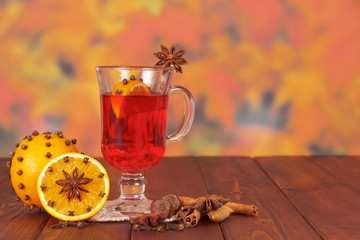Cup of mulled wine on a wooden table with spices