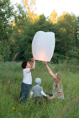 Family of three flying paper lantern outdoor