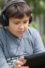 Teenager in headphones using pad outdoor