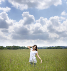 Young woman walks in summer field