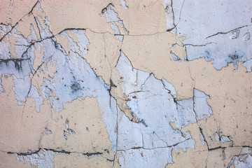 Cracked concrete surface with the remains of sandy-tan paint