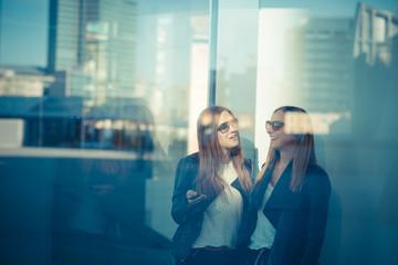 two beautiful young women through glass