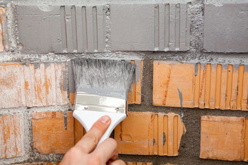 Paint brush with grey color on brick wall