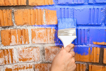 Human hand with blue colored brush painting brick wall