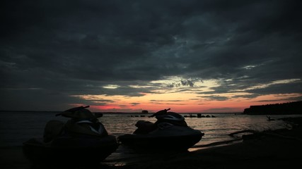 Timelapse. Two jet ski standing on the shore in sunset rays.