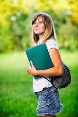 Young female student standing on green grass background