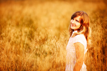 Young woman standing in dry grass field