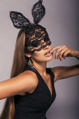 beautiful girl with long hair in black lace bunny mask