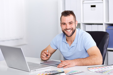 Graphic designer using a graphics tablet in a modern office