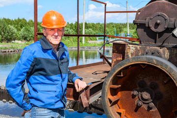 Engineer worker stands near sewage treatment mechanism