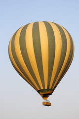 Flying green and yellow hot air balloon