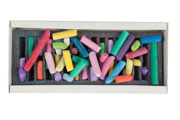 stack of multicolored pastel chalks on box isolated on white bac