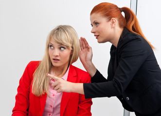 two woman colegues gossip in office