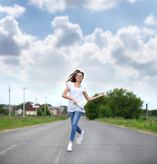 Young woman running along a country road