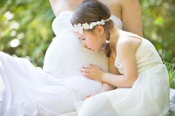 little girl kissing pregnant mother