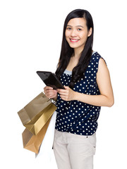 Asian woman with shopping bag and digital tablet