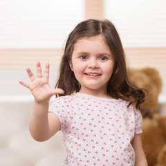 charming little girl showing five.
