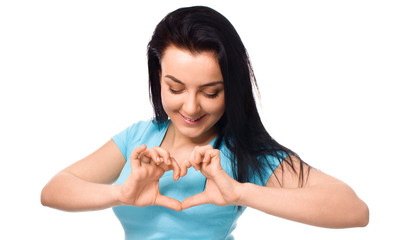 Beautiful young woman showing heart symbol gesture
