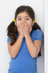 little girl covering face and mouth.