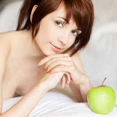 red-haired girl lying with apple