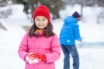 little girl holding snowball and smiling.
