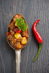 Mexican dish chili con carne in a spoon on a wooden background