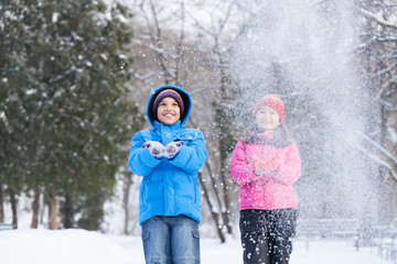 boy and girl throwing snow into air.
