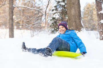 young boy sledding on snow in park.