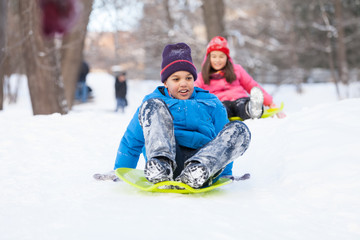 boy and girl sliding on sledges in park.