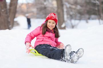 little girl sitting on sledges and sliding.
