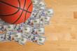 Basketball on pile of one hundred dollar bills