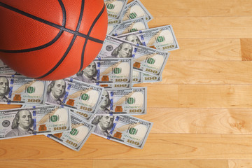 Basketball on pile of one hundred dollar bills