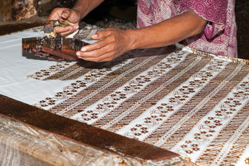 Man stamping batik in workshop