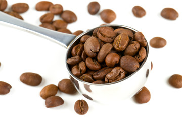 coffee beans in a spoon isolated on white