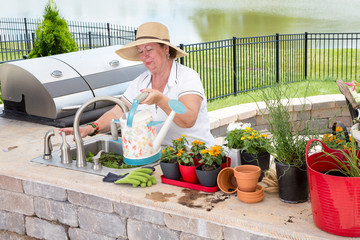 Lady filling a watering can on an outdoor patio