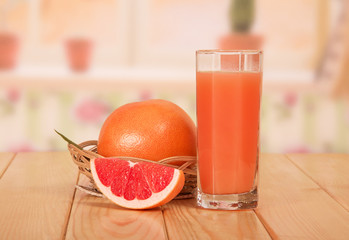 Glass of fresh juice and grapefruit slice close-up
