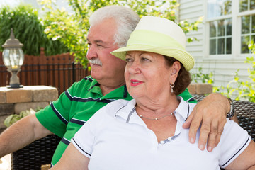 Elderly couple sitting gazing into the distance