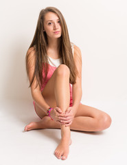 Beautiful young teenager sitting on the ground