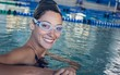 Fit swimmer smiling at camera in the swimming pool