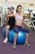 Trainer watching client lift dumbbells on exercise ball
