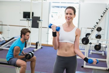 Fit brunette exercising with blue dumbbells smiling at camera