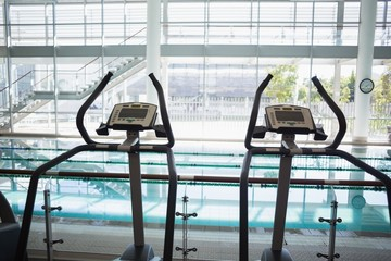 Cross trainer machines overlooking large swimming pool