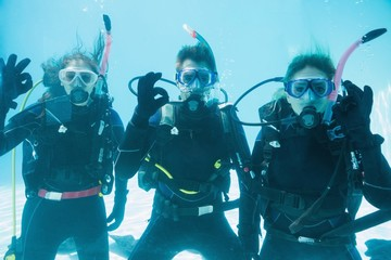 Friends on scuba training submerged in swimming pool looking to