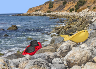 Two empty bright red and yellow kayaks on rocky shore