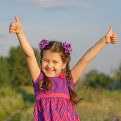 child showing thumbs up outdoors