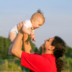 Father and baby playing outdoors.